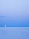 Lonely yacht on horizon. The sailing boat between the sky and the sea Royalty Free Stock Photography