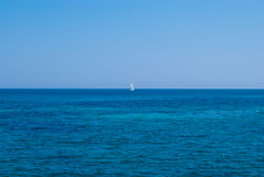 Lonely yacht in an open sea under solid blue sky Stock Images