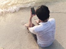 Lonely young Asian man with mobile smart phone sitting on sand of tropical beach. stock photography