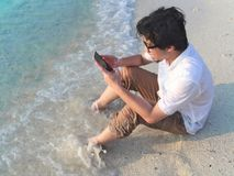 Lonely young Asian man with mobile smart phone sitting on sand of tropical beach. stock images