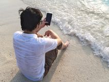 Lonely young Asian man with mobile smart phone sitting on sand of tropical beach. Summer vacations concept. royalty free stock photography