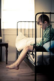 Lonely Young Boy Sitting on Bed Inside his Room Royalty Free Stock Photos