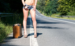 Lonely young brunette woman walking on the side of the road with an old suitcase and a sign for hitchhiking. Lonely young brunette woman walking on the side of Royalty Free Stock Photo