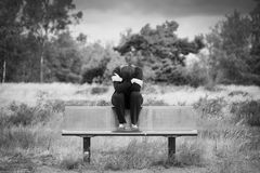 Lonely young depressed sad woman sitting on a bench with arms crossed in front of her face. Monochrome portrait. stock photo