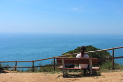 Lonely young female hiker, takes a rest in front of turquoise waters after a long morning walk, Calella de la Costa, Barcelona. Stock Image