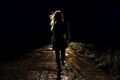 Lonely young frightened woman on an empty night road runs away in the light of the headlights of her car. Blonde lonely young frightened woman on an empty night stock image