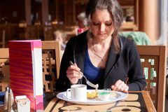 A lonely young girl has breakfast in the restaurant with cakes and tea.  Royalty Free Stock Images