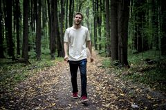 Lonely young male hipster in casual walks in autumn dark moody forest with fallen leaves stock photos