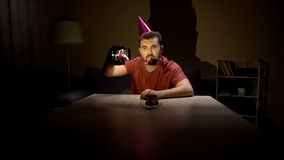 Lonely young man celebrating birthday taking selfie, depression, single life stock images