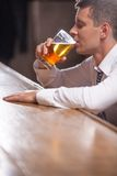 Lonely young man drinking alone at the pub. Stock Photo