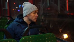 Lonely young man rides in a tram in the night.  stock footage