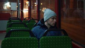 Lonely young man rides in a tram in the night.  stock video footage