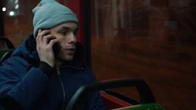 Lonely young man rides in a tram and talks on the phone in the night.  stock video