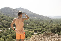 Lonely young man stands on the mountain and looks into the distance. concept - research, search, goals, move forward, achieve succ Royalty Free Stock Photo