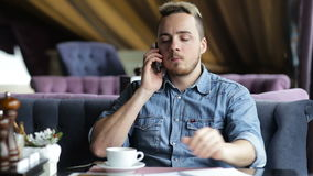 Lonely young man talking on the phone in restaurant stock video footage