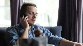 Lonely young man talking on the phone in restaurant stock footage