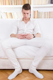 Lonely young man in white texting message on cellphone Royalty Free Stock Images