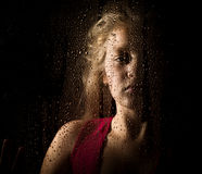Lonely young sad girl behind the window with drops.  Royalty Free Stock Photo