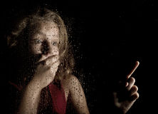Lonely young sad girl behind the window with drops. frightened young woman shows on something.  Royalty Free Stock Photos
