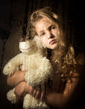 Lonely young sad girl behind the window with drops, holding teddy bear and crying.  Royalty Free Stock Photography