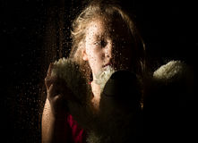 Lonely young sad girl behind the window with drops, holding teddy bear and crying.  Royalty Free Stock Images