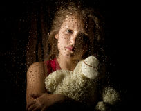 Lonely young sad girl behind the window with drops, holding teddy bear and crying Royalty Free Stock Photos