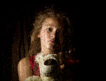 Lonely young sad girl behind the window with drops, holding teddy bear and crying.  Stock Image