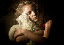 Lonely young sad girl behind the window with drops, holding teddy bear and crying.  Stock Images