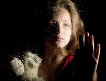 Lonely young sad girl behind the window with drops, holding teddy bear and crying Royalty Free Stock Images