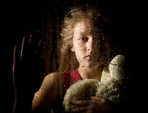 Lonely young sad girl behind the window with drops, holding teddy bear and crying Royalty Free Stock Photography
