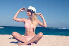 Lonely young woman sitting on the tropical beach by the sea with hat and in the swimsuit. Bali island vacation Royalty Free Stock Photography