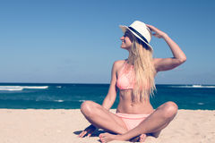 Lonely young woman sitting on the tropical beach by the sea with hat and in the swimsuit. Bali island vacation Stock Image