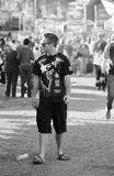 Lonely young teen man standing out from the crowd at carnival Royalty Free Stock Photo