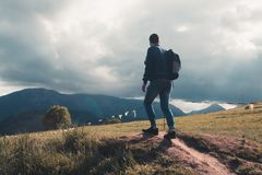 Lonely young tourist guy with backpack climbed to the top and lo stock images