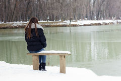 Lonely young woman. A lonely young woman sitting on a bench beside the lake, winter time Royalty Free Stock Photo
