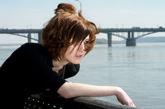 Lonely young woman feeling very sad. Lonely beautiful young woman at the river embankment feeling very sad Royalty Free Stock Image