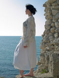 Lonely Young Woman Looks on Sea. Lonely young woman looking on sea white dress Royalty Free Stock Photo