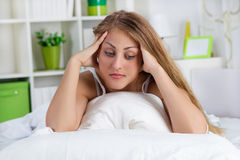Lonely young woman lying in bed Stock Image