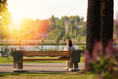Lonely young woman sitting on a bench in the park Stock Images