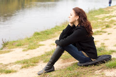 Lonely young woman sitting on a lake shore. Lonely young woman sitting on a cushion on the ground on the shore above a tranquil lake daydreaming as she stares Stock Photo
