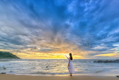 Lonely young woman stands alone on the beach looking towards the end of the vast horizon. Mui Ne, Vietnam - December 6th, 2016: Lonely young woman stands alone Royalty Free Stock Images