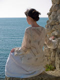 Lonely Young Woman on Stone Looking to Sea. Lonely young woman looking on sea white dress sitting on stone Stock Images