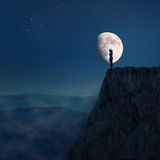 Lonely young woman on top of a cliff at night Stock Photo