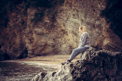 Lonely young woman traveler relaxing on a big cliff stone on the beach looking at wild mountain scenery in retro vintage s Royalty Free Stock Photos