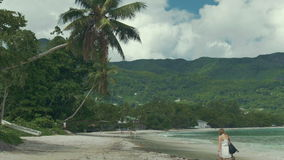 Lonely young woman walking on the beach at Mahe, Seychelles. Woman wearing dress on beach at Seychelles, Mahe. Anse Beau Vallon tropical beach, Mahe island stock video footage