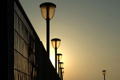 The loner. Sunset with a row of lamps and fence stock photography