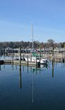 Loner. Sailboat docked all alone in large harbor with mast fully reflected in the water Royalty Free Stock Photography