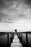 Loner with umbrella. A lonely guy standing with umbrella near a lake Stock Images