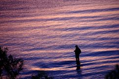 Fishing at sunset. Lonesome angler fishing at the shore at sunset stock photography