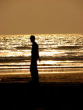 Lonesome Beach. A lonely guy staring at the sea Royalty Free Stock Images